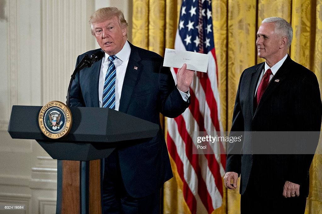U.S. President Donald Trump holds up an envelope that was left for him in the Oval Office by former President Barack Obama next to U.S. Vice President Mike Pence, right, during a swearing in ceremony of White House senior staff in the East Room of the White House on January 22, 2017 in Washington, DC. Trump today mocked protesters who gathered for large demonstrations across the U.S. and the world on Saturday to signal discontent with his leadership, but later offered a more conciliatory tone, saying he recognized such marches as a 'hallmark of our democracy.'