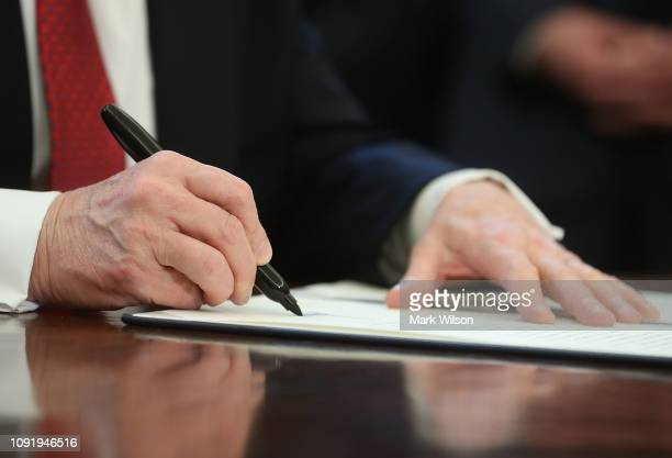 S President Donald Trump holds up an executive order he signed during a meeting with members of Congress and American manufacturers to strengthen the...