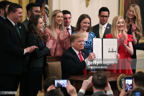 S President Donald Trump holds up an executive order he signed protecting freedom of speech on college campuses during a ceremony in the East Room at...