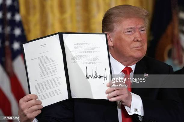 S President Donald Trump holds up an executive order that he signed during a meeting of the National Space Council at the East Room of the White...