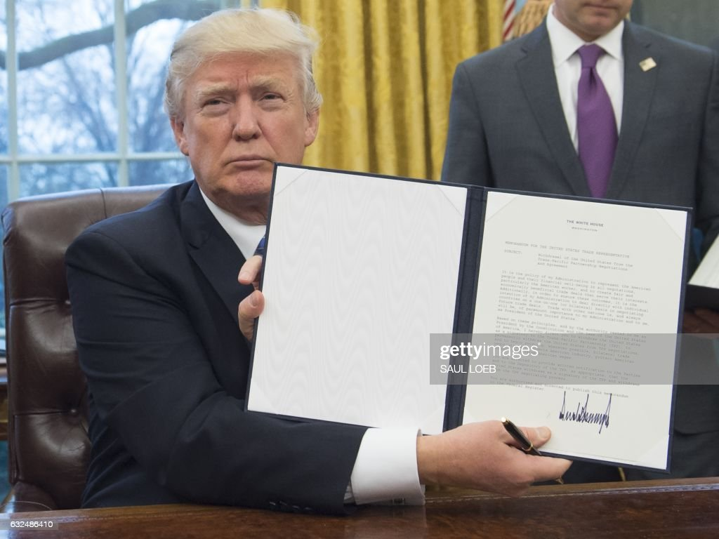 President Donald Trump holds up an executive order withdrawing the US from the Trans-Pacific Partnership after signing it in the Oval Office of the White House in Washington, DC, January 23, 2017. Trump the decree Monday that effectively ends US participation in a sweeping trans-Pacific free trade agreement negotiated under former president Barack Obama. /