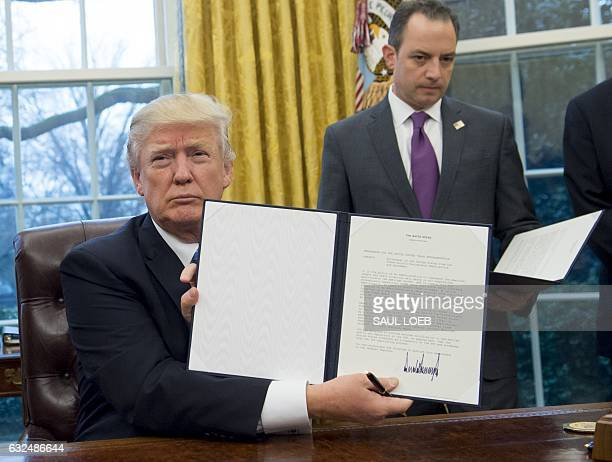US President Donald Trump holds up an executive order withdrawing the US from the TransPacific Partnership after signing it alongside White House...