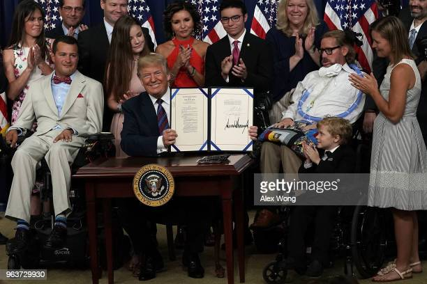 S President Donald Trump holds up and show a bill during a bill signing ceremony at the South Court Auditorium of the Eisenhower Executive Building...