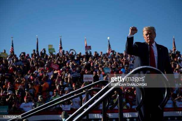 President Donald Trump holds up his fist as he leaves after speaking during a Make America Great Again rally at Phoenix Goodyear Airport October 28...