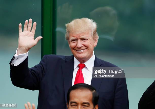 US President Donald Trump holds up his hand during the 'family photo' at the AsiaPacific Economic Cooperation leaders' summit in the central...