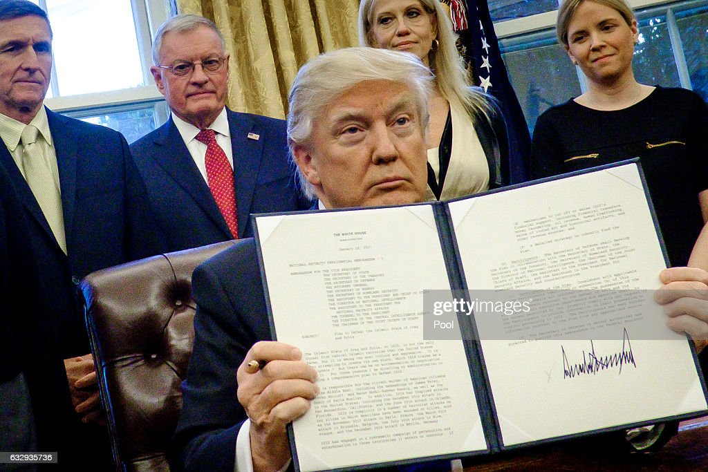 President Donald Trump holds up one of the executive actions that he signed in the Oval Office on January 28, 2017 in Washington, DC. The actions outline a reorganization of the National Security Council, implement a five year lobbying ban on administration officials and a lifetime ban on administration officials lobbying for a foreign country and calls on military leaders to present a report to the president in 30 days that outlines a strategy for defeating ISIS.