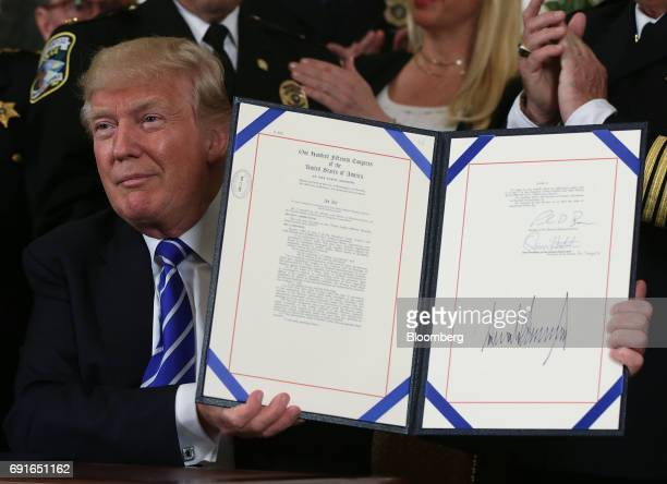 US President Donald Trump holds up signed bill S 419 the Public Safety Officers Benefits Improvement Act of 2017 in the Diplomatic Reception Room of...