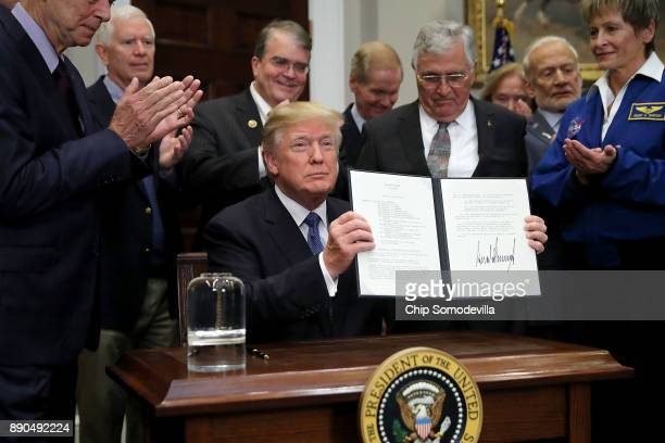 US President Donald Trump holds up 'Space Policy Directive 1' after signing it during a ceremony with NASA astronauts Peggy Whitson Buzz Aldrin and...