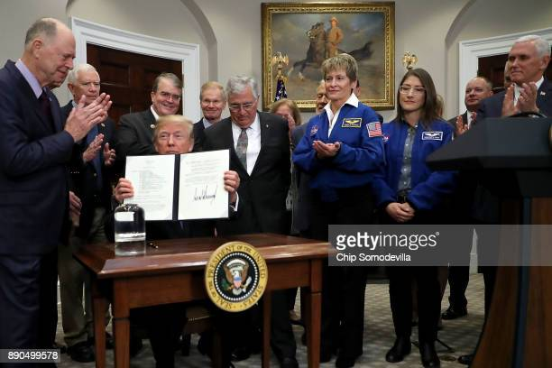 S President Donald Trump holds up 'Space Policy Directive 1' after signing it during a ceremony with Vice President Mike Pence Sen Bill Nelson and...