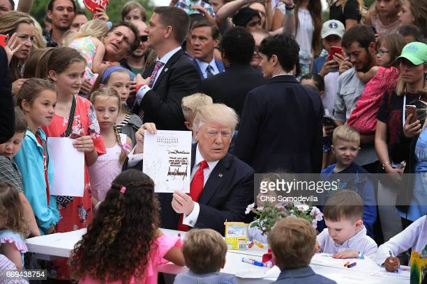 S President Donald Trump holds up the coloring sheet he wrote on while joining children at a craft table during the 139th Easter Egg Roll on the...