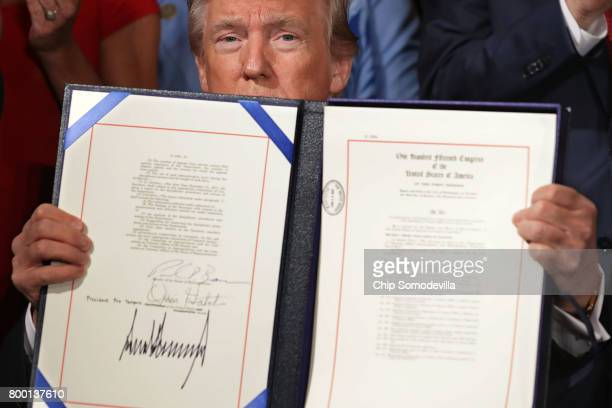 S President Donald Trump holds up the Department of Veterans Affairs Accountability and Whistleblower Protection Act of 2017 after signing it during...