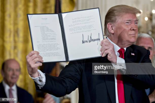 US President Donald Trump holds up the Space Policy Directive3 after being signed during a National Space Council meeting in the East Room of the...
