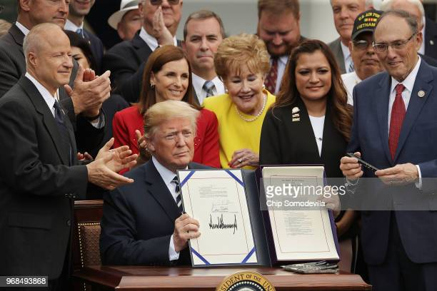 S President Donald Trump holds up the Veterans Affairs Mission Act he signed during a ceremony with members of Congress including House Veterans...