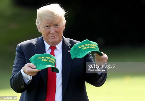 S President Donald Trump holds up two hats that say Make Our Farmers Great Again as he departs the White House August 30 2018 in Washington DC Trump...