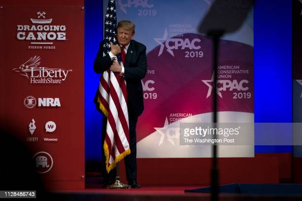 S President Donald Trump hugs a US flag as he takes the stage at CPAC in National Harbor Maryland Saturday March 2 2019