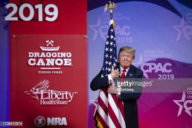 US President Donald Trump hugs an American flag before speaking during the Conservative Political Action Conference in National Harbor Maryland US on...