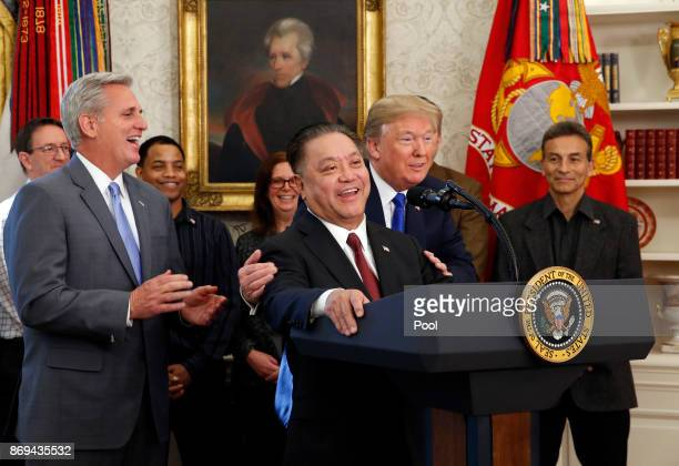 US President Donald Trump hugs Broadcom CEO Hock Tan as Tan announces the repatriation of his company's headquarters to the United States from...