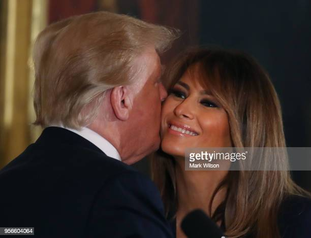S President Donald Trump hugs first lady Melania Trump during an event to celebrate military mothers and spouses in The East Room at the White House...