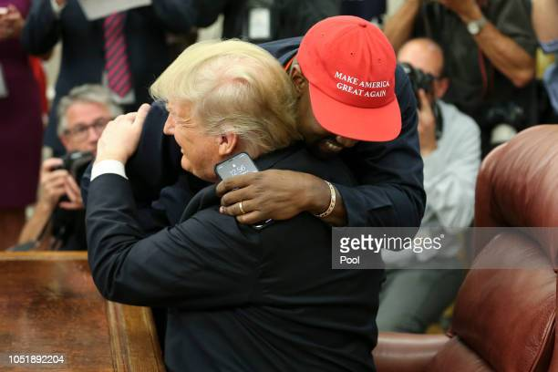 US President Donald Trump hugs rapper Kanye West during a meeting in the Oval office of the White House on October 11 2018 in Washington DC