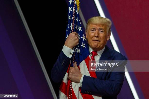 President Donald Trump hugs the flag at the annual Conservative Political Action Conference at Gaylord National Resort & Convention Center February...