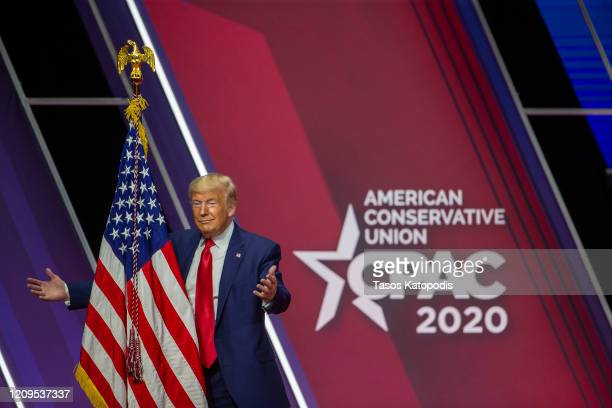 President Donald Trump hugs the flag of the United States of America at the annual Conservative Political Action Conference at Gaylord National...