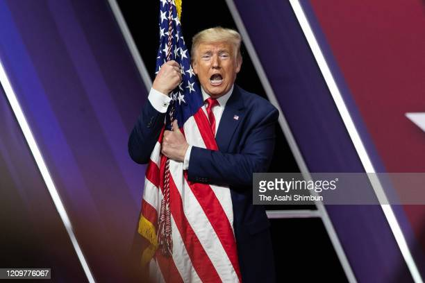 S President Donald Trump hugs the flag of the United States of America at the annual Conservative Political Action Conference at Gaylord National...