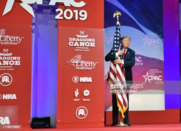 President Donald Trump hugs the US flag as he arrives to speak at the annual Conservative Political Action Conference in National Harbor Maryland on...