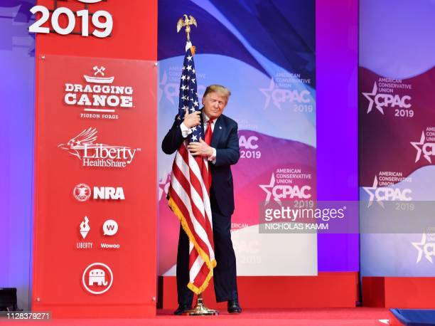 US President Donald Trump hugs the US flag as he arrives to speak at the annual Conservative Political Action Conference in National Harbor Maryland...