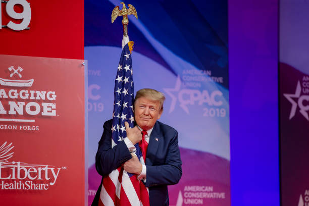 President Donald Trump hugs the U.S. Flag during CPAC 2019 on March 02, 2019 in National Harbor, Maryland. The American Conservative Union hosts the...