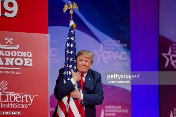 US President Donald Trump hugs the US flag during CPAC 2019 on March 02 2019 in National Harbor Maryland The American Conservative Union hosts the...