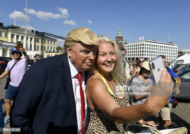 US' President Donald Trump impersonator Dennis Alan poses for pictures in front of the presidential palace on July 15 ahead of the arrival of US...