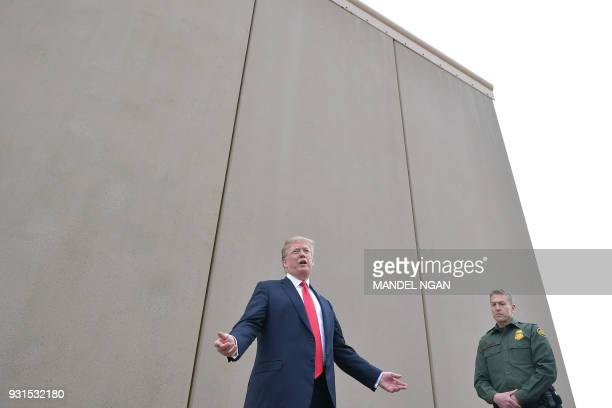 US President Donald Trump inspects border wall prototypes with Chief Patrol Agent Rodney S Scott in San Diego California on March 13 2018 / AFP PHOTO...