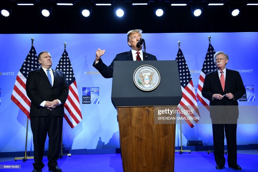 President Donald Trump (C) is accompanied by US Secretary of State Mike Pompeo (L) and US National Security Advisor John Bolton (R) as he addresses a press conference on the second day of the North Atlantic Treaty Organization (NATO) summit in Brussels on July 12, 2018.