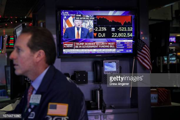 President Donald Trump is displayed on a monitor as a trader works at his desk ahead of the closing bell on the floor to he New York Stock Exchange ,...