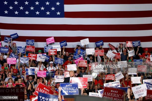 President Donald Trump is engulfed by supporters holding signs during a rally at the International Air Response facility on October 19 2018 in Mesa...
