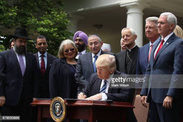 S President Donald Trump is flanked by clergy members as he signs an Executive Order on Promoting Free Speech and Religious Liberty during a National...