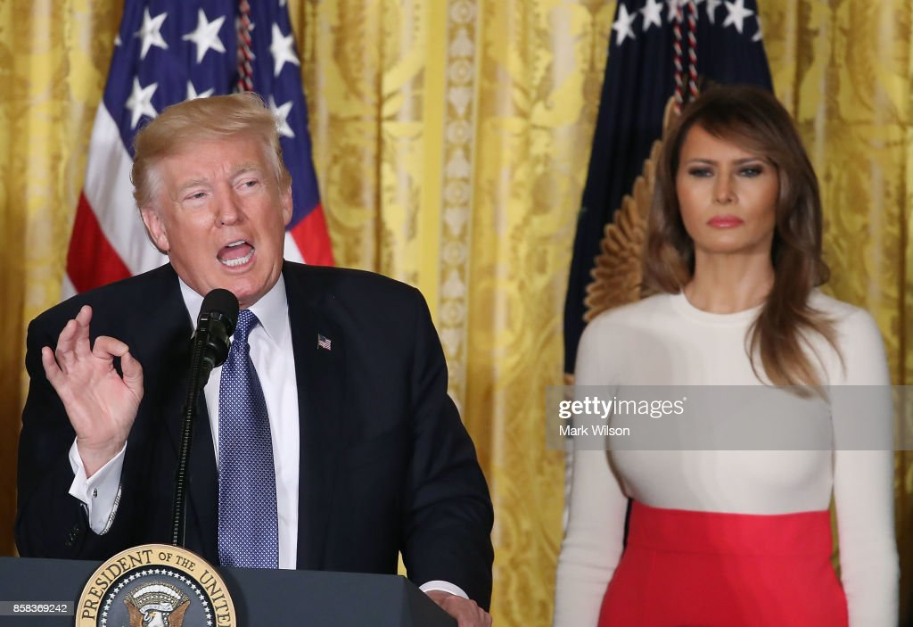U.S. President Donald Trump is flanked by first lady Melania Trump as he speaks to guests gathered in the East Room of the White House to celebrate Hispanic Heritage Month, on October 6, 2017 in Washington, DC.