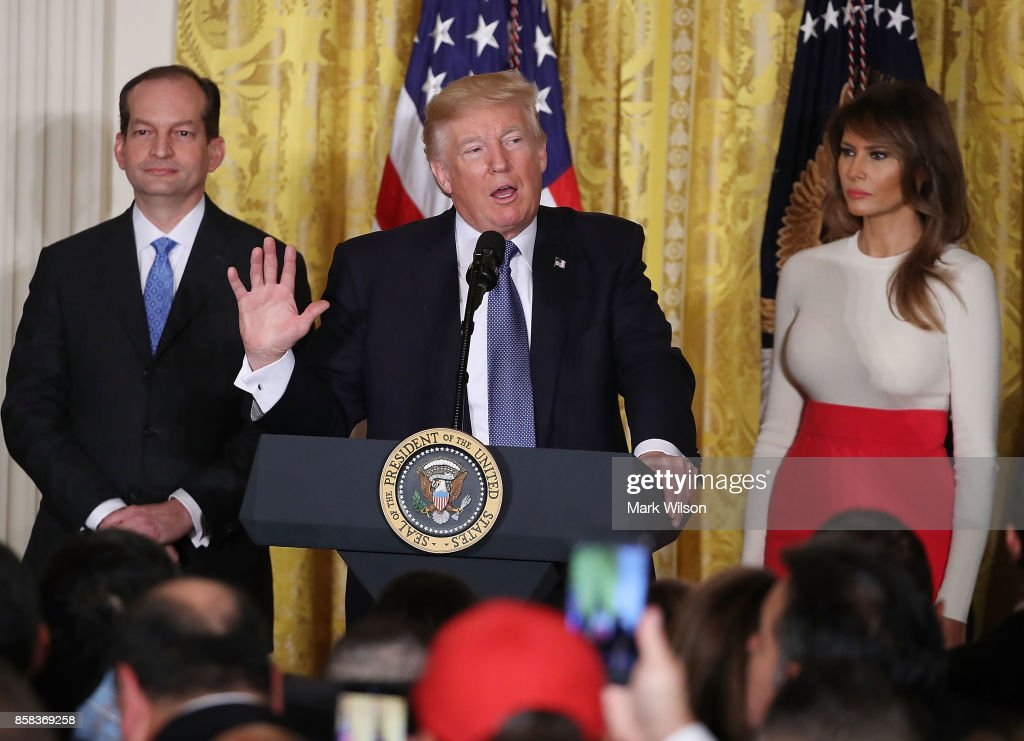 U.S. President Donald Trump is flanked by Labor Secretary Alex Acosta (L) and first lady Melania Trump as he speaks to guests gathered in the East Room of the White House to celebrate Hispanic Heritage Month, on October 6, 2017 in Washington, DC.