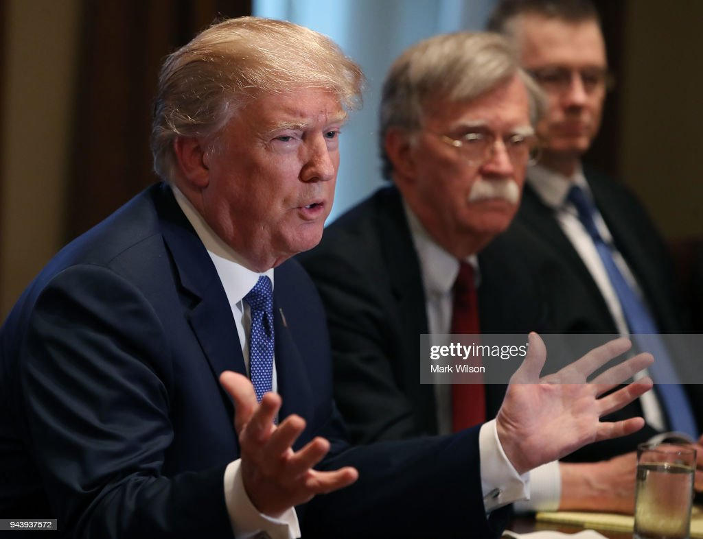U.S. President Donald Trump is flanked by National Security Advisor John Bolton as he speaks about the FBI raid at his lawyer Michael Cohen's office, while receiving a briefing from senior military leaders regarding Syria, in the Cabinet Room, on April 9, 2018 in Washington, DC. The FBI raided the office of Michael Cohen on Monday as part of the ongoing investigation into the president's administration.