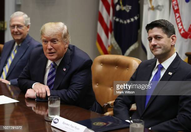 President Donald Trump is flanked by Senate Majority Leader Mitch McConnell and House Majority Leader Paul Ryan while speaking during a meeting with...