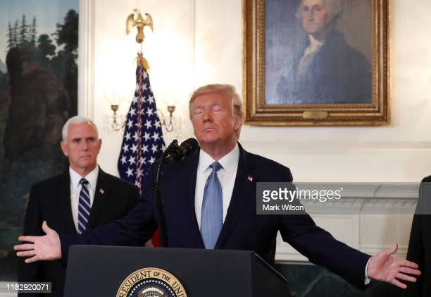 S President Donald Trump is flanked by Vice President Mike Pence while making statement in the Diplomatic Room at the White House on October 23 2019...