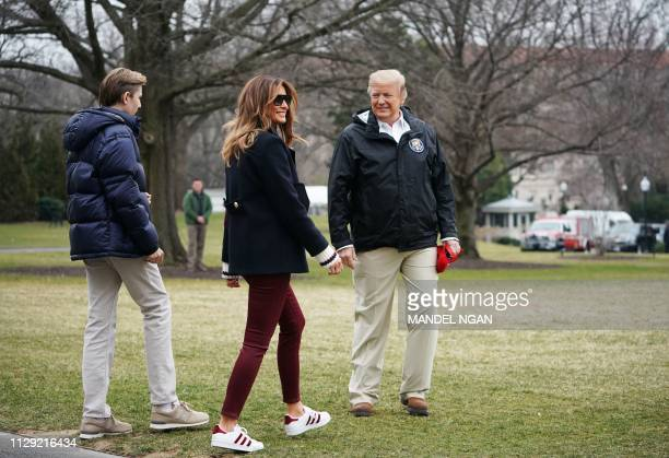 US President Donald Trump is joined by First Lady Melania Trump and their son Barron before boarding Marine One to depart from the South Lawn of the...