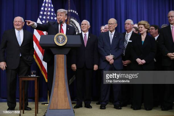 President Donald Trump is joined on stage by members of Congress, farming and livestock representatives and others during the signing ceremony for...