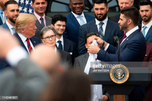 US President Donald Trump is presented with a jersey by professional baseball player JD Martinez as the president welcomes the 2018 World Series...