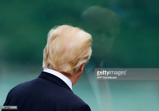 US President Donald Trump is reflected in glass during the 'family photo' at the AsiaPacific Economic Cooperation leaders' summit in the central...