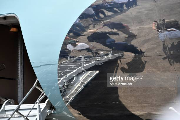 US President Donald Trump is reflected on Air Force One as he arrives in Lake Charles Louisiana on September 2 2017 Trump is touring areas affected...