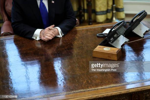 President Donald Trump is reflected on the resolute desk as he speaks during a meeting with Chinese Vice Premier Liu He, right, in the Oval Office of...