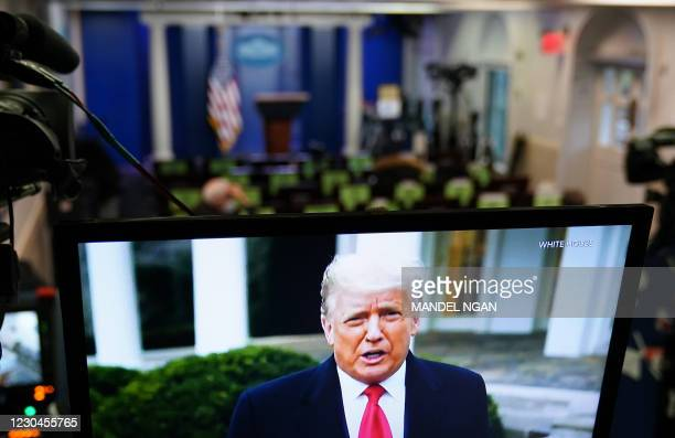 President Donald Trump is seen on TV from a video message released on Twitter addressing rioter at the US Capitol, in the Brady Briefing Room at the...