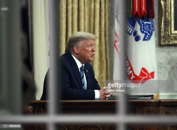 S President Donald Trump is seen through a window in the Oval Office as he addresses the nation on the response to the COVID19 coronavirus on March...