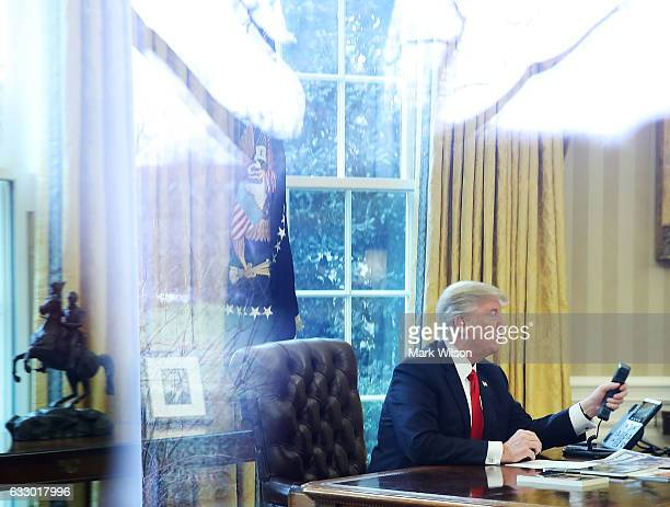 President Donald Trump is seen through a window making a phone call to King of Saudi Arabia Salman bin Abd alAziz Al Saud in the Oval Office of the...